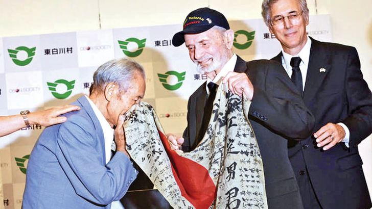 Marvin Strombo handing the flag back to Sadao Yasue's younger brother Tatsuya Yasue