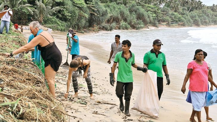 Tourists and hotel staff participating in the beach cleanup campaign.