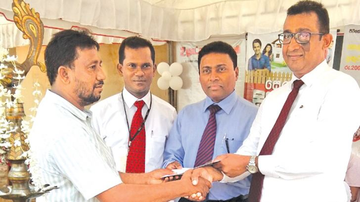 Dilum Amarasinghe-Head of leasing, Seylan Bank  handing over the vehicle key and the documents to Mubarak Moujood, who was the first leasing customer during the promotion, while Rajitha Gajanayake- Area manager North West II and Rayshantha Fernando-Manager, Puttalam branch look on.