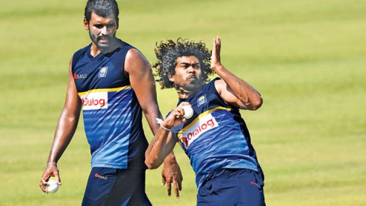 Lasith Malinga bowls at practice watched by team mate Thisara Perera at the Pallekele International Stadium yesterday ahead of today's second ODI against India. - AFP