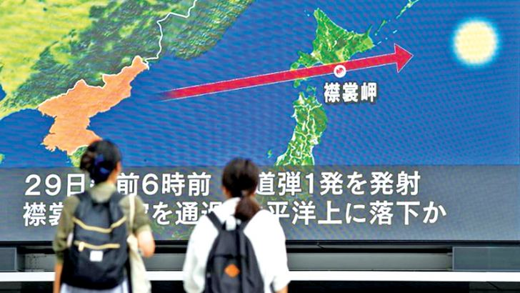 Women looking at a large TV screen showing news about North Korea's missile launch in Tokyo, Japan yesterday.