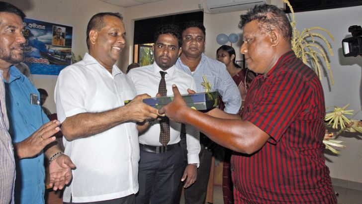 Minister Mahinda Amaraweera distributing E-log books