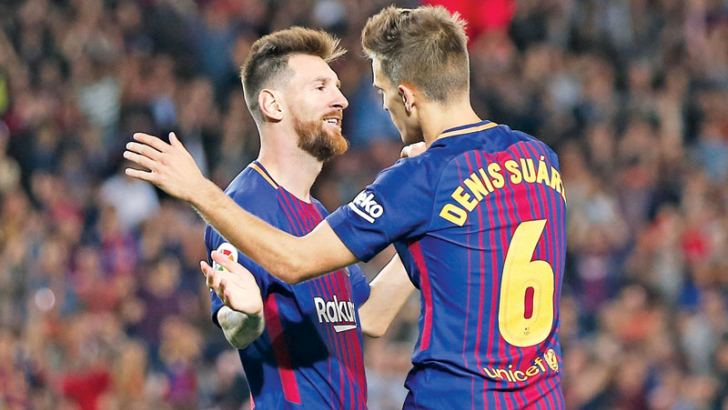 Barcelona's midfielder from Spain Denis Suarez (R) celebrates with Barcelona's forward from Argentina Lionel Messi after scoring during the Spanish league football match FC Barcelona against SD Eibar at the Camp Nou stadium in Barcelona on September 19.- AFP