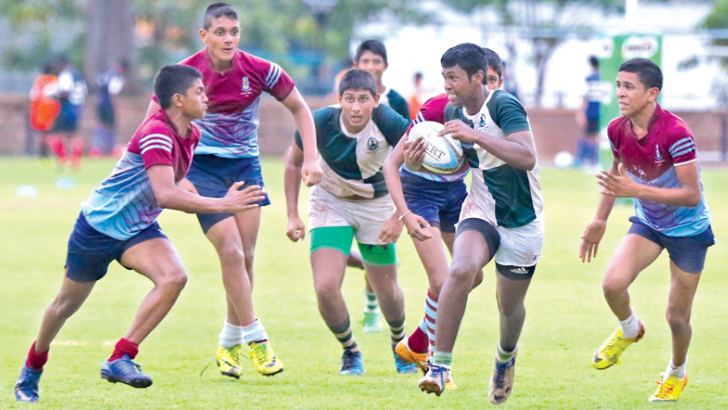 Action at the Under-16 Milo All-Island 15-A-Side Rugby Tournament Cup Championship semi-final between Isipathana College (green) and Dharmaraja College .
