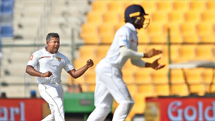 Rangana Herath celebrates the dismissal of Asad Shafiq for 39 on the fourth day of the first Test at Abu Dhabi on Sunday. AFP