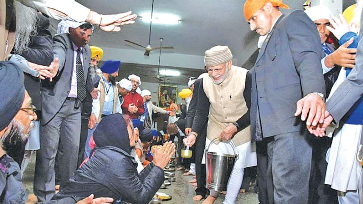 Prime Minister Narendra Modi serves langar during his visit at the Golden Temple in Amritsar on Saturday.