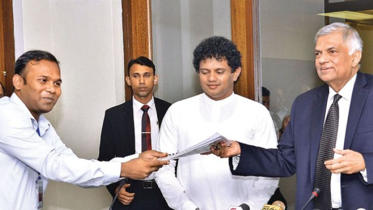 Prime Minister Ranil Wickremesinghe receiving the report in Parliament from AFRIEL organisation members yesterday. Picture by Saaman Mendis.