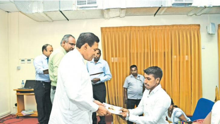 Health Minister Dr. Rajitha Senaratne hands over ​an appointment letter to one of the field assistants during the ceremony.