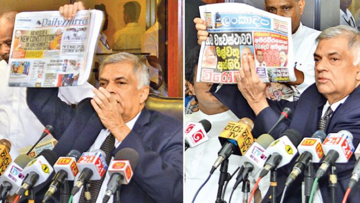 Prime Minister Ranil Wickremesinghe displaying the front pages of newspapers that misleadingly carried the Malwatte Mahanayake Thera's picture. Pictures by Saman Mendis