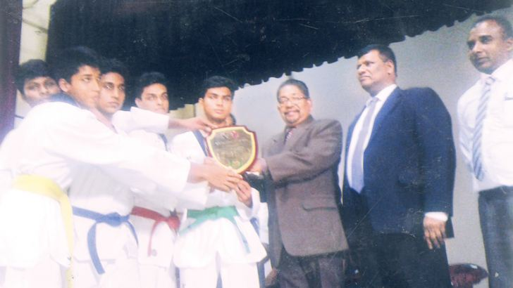 Sports Directors K.M. Ratnayake and Kantha Siri Meegamuwage with WP Councillor Jagath Angage presenting the Boys Overeall Talekwondo All Island Championship Trophy to the St. Sebastian s Central College team.