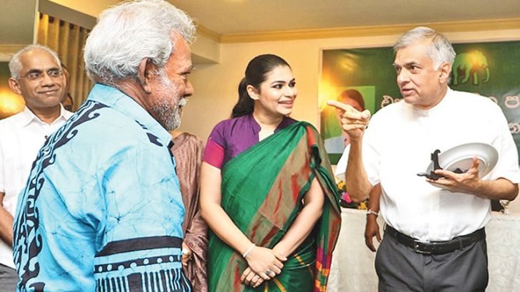 Prime Minister Ranil Wickremesinghe presenting a token to one of the longstanding party supporters in Ratmalana yesterday.  Picture by Saman Sri Wedage.