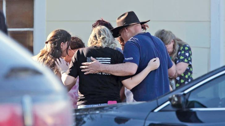A group gathers in prayer outside the Sutherland Springs Community Building.