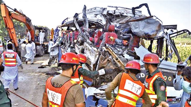 A Pakistani rescue team working on the wreckage of a bus after a deadly accident.