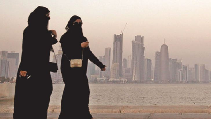Women walk past buildings as the sun sets in Doha, Qatar.