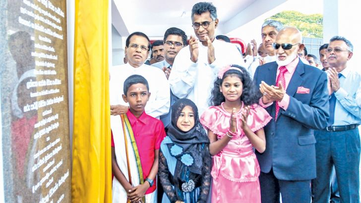 President Maithripala Sirisena unveiling the plaque marking the opening of the housing complex while Ministers Patali Champika Ranawaka, A. H. M. Fowzie and others look on. Picture by President's Media