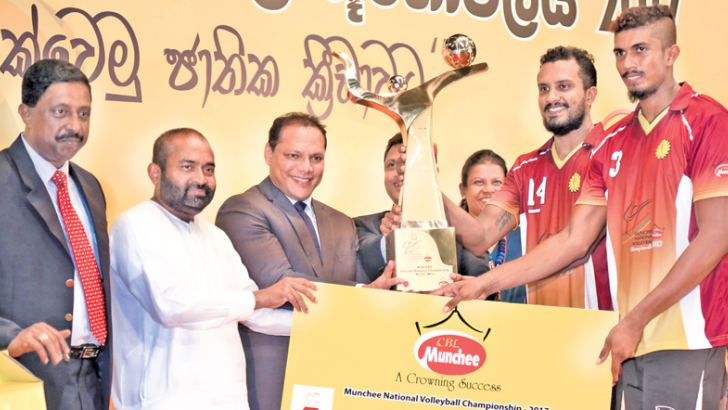 The skipper of the victorious men's Super League Ceylon Electricity Board receiving the trophy from Sports Minister Dayasiri Jayasekara and the President of the Volleyball Federation of Sri Lanka and Minister of Power and Sustainable Energy Ranjith Siyambalapitiya.