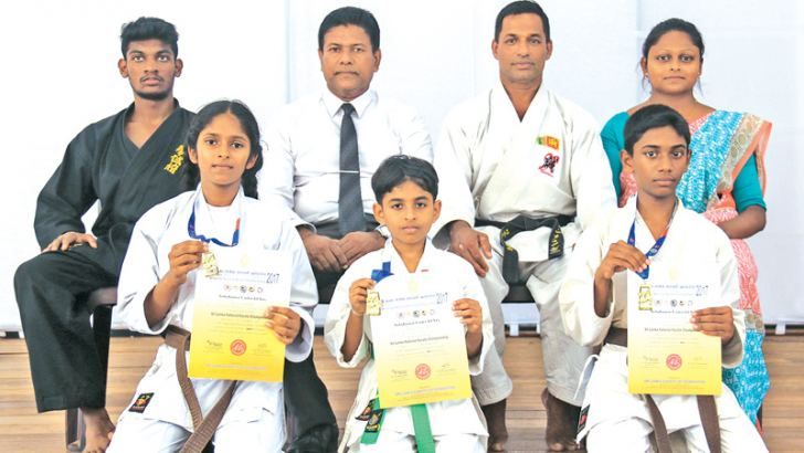 Victorious Clayton International karatekas with their gold medals and certificates: Front row kneeling from left: Niduki Archana Devindi, Dahami Dilanji Hasthamalika and Jathya Nethmina Jayasinghe. Back row from left: Assistant coach Hasitha Jayanath, Principal Gamini Jayasekara, Head Coach G.K. Tennakoon and Teacher In-Charge Kasuni Weerawarna.