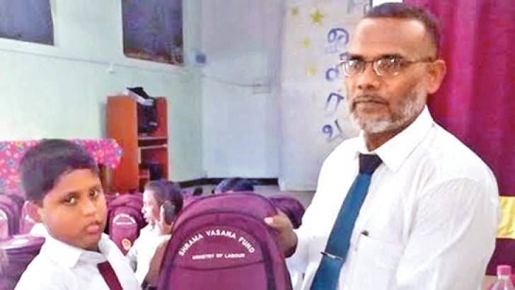 A student being presented a schoolbag. Picture by I. L. M. RIZAN, Addalaichenai Central Corr.