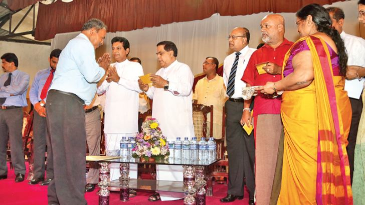 Minister Nimal Siripala De Silva handing over a cheque to one of the affected SLTB employees.
