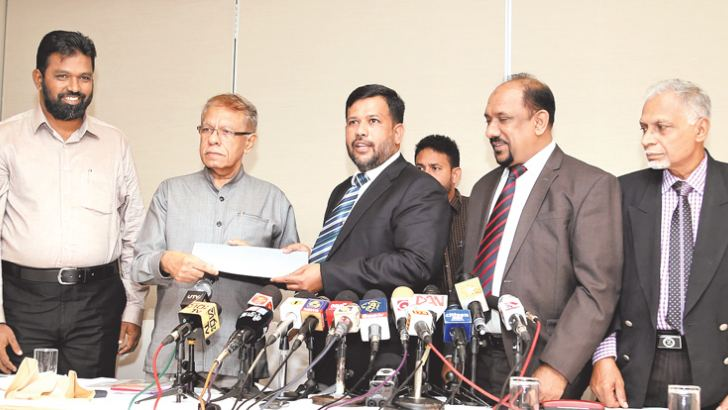Industry and Commerce Minister Rishad Bathiudeen and ACMC Leader Rishad Bathiudeen, and United Peace Alliance (UPA) Leader MP Basheer Segu Dawood exchanging the agreement signed between the two parties for the new UPA party.