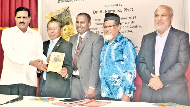 Independent Television Network former Director Hashim Omar receiving the first copy of the book from chief guest Malaysian High Commissioner to Sri Lanka Wan Zaidi Wan Abdullah. Picture by  Ruzaik Farook
