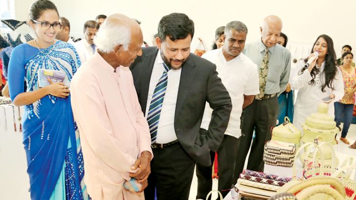 Minister Bathiudeen views palmyrah handicrafts on display at Shilpa Saviya crafts entrepreneur exhibition held at Jaguar Land Rover showroom, Colombo on December 8, made by M. Mahindadasa (second from left), a craftsman from Buttala as Chairperson of National Crafts Council, Heshani Bohollagama (far left) looks on.