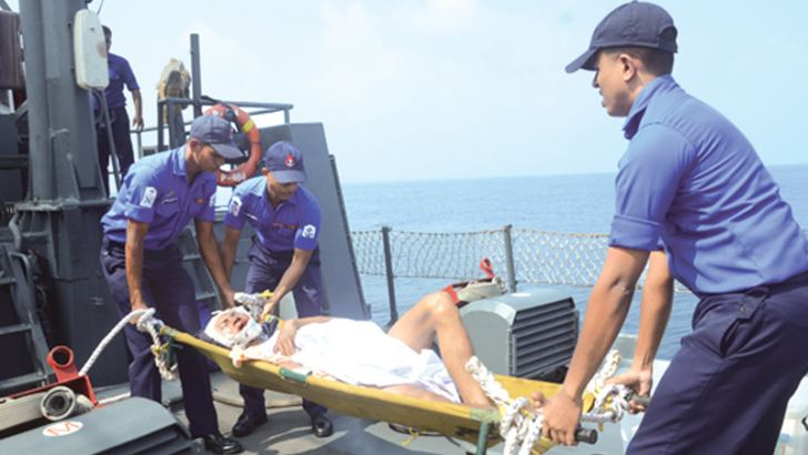 Navy personnel getting ready to transfer the patient onboard.
