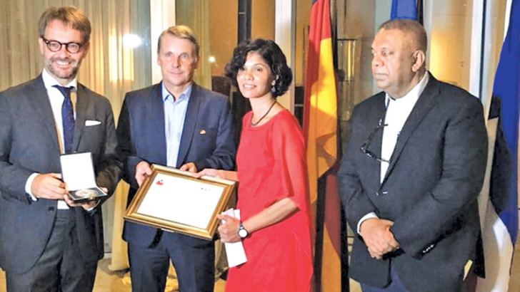 Finance Minister Mangala Samaraweera looks on as Shreen Abdul Saroor receives the award