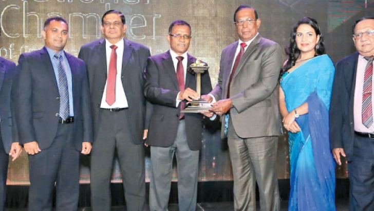 Philip J. Wewita, Chairman of Pussalla receiving the award from Chairman  Bank of Ceylon. Asela de Livera Deputy President of National Chamber,  Dilshan J. Wewita Managing Director and Dr. Premasiri General Manager of Pussalla look on.
