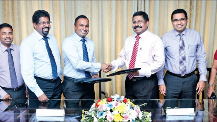 Commercial Bank's Executive Director/Chief Operating Officer S. Renganathan (third from right) and Hayleys Agriculture Director Lushan Nalinda Abesekara exchange the agreement in the presence of senior representatives of the two companies.