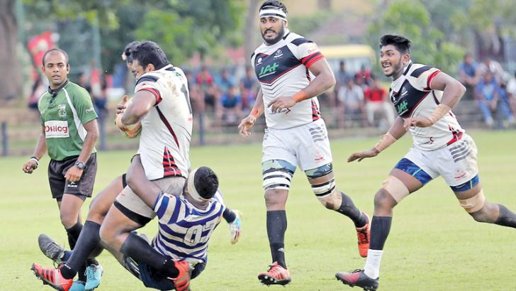 A CH and FC player is well tackled by Navy sports club defender Stefan Gregory with more support coming from Sajith Saranga and. Sasanka Ariyaratne in their Dialog A division league rugby match played at Race Course ground yesterday which CH and FC won 27-24. (Picture by Rukmal Gamage)