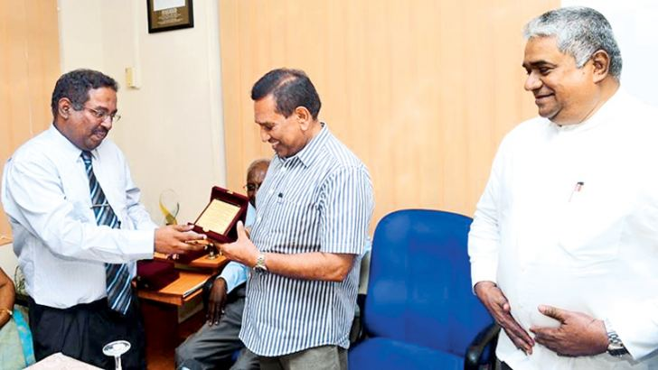 Deputy Director General of the Health Ministry Planning Division, Sathasivam Shridharan, hands over a token of appreciation to ​Health Minister Dr. Rajitha Senaratne while Health Deputy Minister Faizal Kassim looks on.