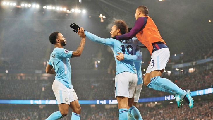 Manchester City's Raheem Sterling celebrates scoring their third goal with teammates.