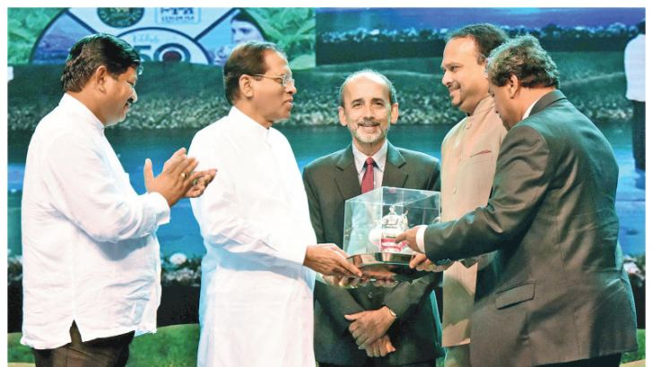 The first-ever National Tea Awards were held to mark the 150th anniversary of Ceylon Tea at Nelum Pokuna with President Maithripala Sirisena as the Chief Guest recently where the contributions and achievements made by individuals and companies in several fields of the tea industry were recognised. Awards were also presented to the best tea plucker, male and female, and tea small holders. Here Plantation Industries Minister Navin Dissanayake at the Nelum Pokuna presenting a memento to President Sirisena.