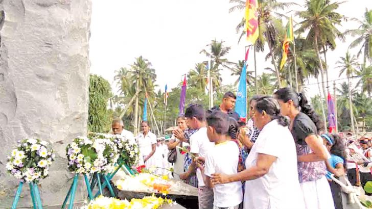 Relatives of the tsunami victims offering flowers at the Peraliya tsunami memorial.  Picture by Mahinda P.Liyanage- Galle Central Special Corr.