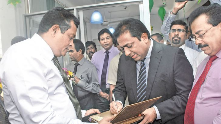 Education Minister Akila Viraj Kariyawasam signs the guest book at the opening of the JSS office in Colombo 3.  Picture by Siripala Halwala
