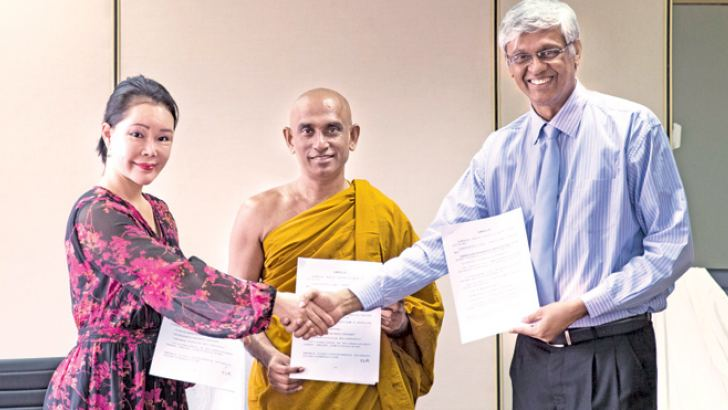 Luang Yizhen, a representative of China LvHai Technology Group, the founder of Sadaham Sevana, the Venerable Athuraliye Rathana Thera and the Chairman of the Strategic Enterprise Management Agency Asoka Abeygunawardana after signing the agreement.