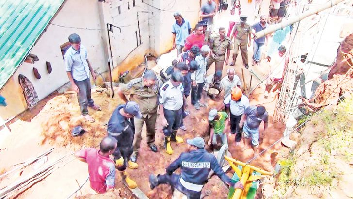 Neighbours assisted by the Kandy Municipal Fire officers trying to rescue the casualties. Picture by Asela Kuruluwansa