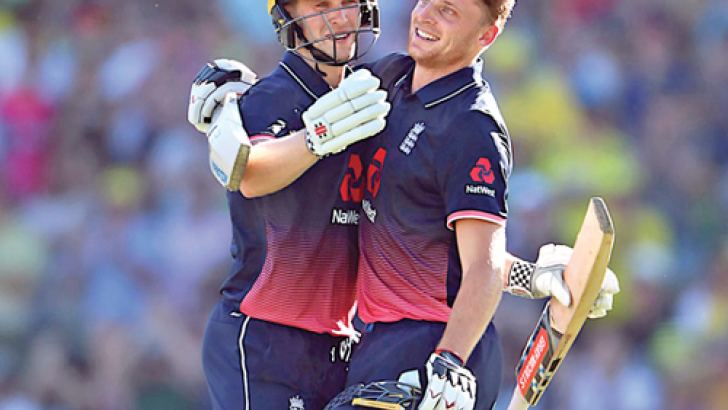 England batsman Chris Woakes congratulates Jos Buttler after he reached his century during the third one-day international against Australia at Sydney on Sunday. AFP