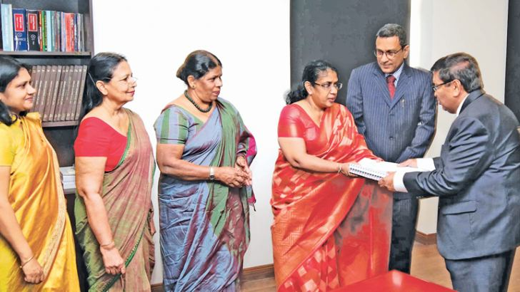 Retired Supreme Court Judge, Justice Saleem Marsoof presents the report to Justice Minister Thalatha Athukorale