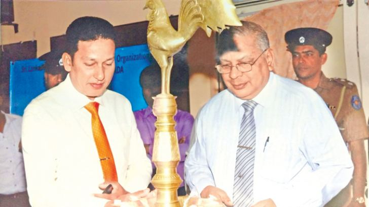 Provincial Education Ministry Secretary H. E. M. W. G. Dissanayake lighting the oil lamp, while project chairperson Lion S. Ramachandran looks on.