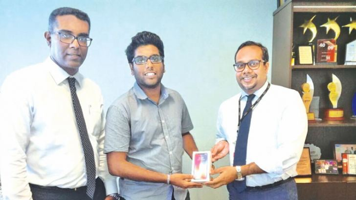 The winner of the iPhone X promotion Dulvin Witharane receiving his gift from Tilan Wijeyesekera, Deputy General Manager Retail Banking and Dinesh Jebamani, Chief Manager  Liability Products and New Age Media.