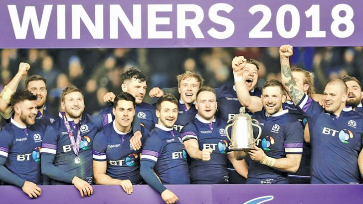 Scotland's John Barclay holds the Calcutta Cup trophy as his team mates celebrate after victory over England.
